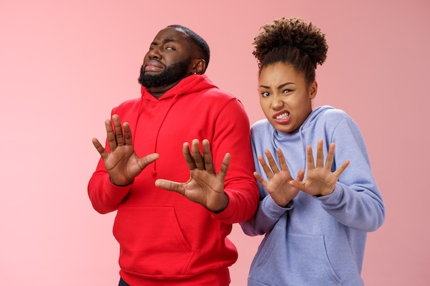 Studioaufnahme paar afroamerikanische freunde frau mann kriecht ekel abneigung fühlen sich unbeholfen widerstrebend zurücktreten handflächen defensiv ablehnend ablehnen versuch stinkendes produkt, stehend rosa hintergrund