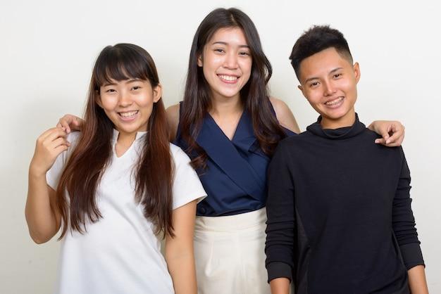 Studioaufnahme von drei jungen schönen asiatischen frauen als freunde zusammen vor weißem hintergrund