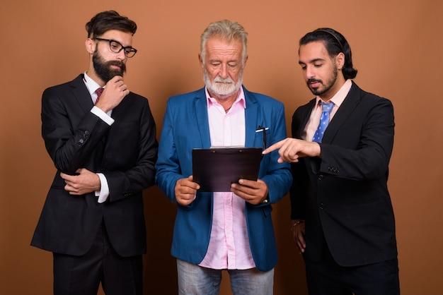 Studioaufnahme von drei multiethnischen bärtigen geschäftsleuten zusammen vor braunem hintergrund