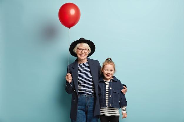 Studioaufnahme von fröhlicher enkelin und großmutter umarmen sich zusammen, kommen auf party