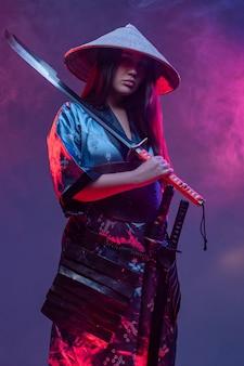 Studioaufnahme von futuristischen frauensamurai mit katana vor hintergrund mit neonbeleuchtung.