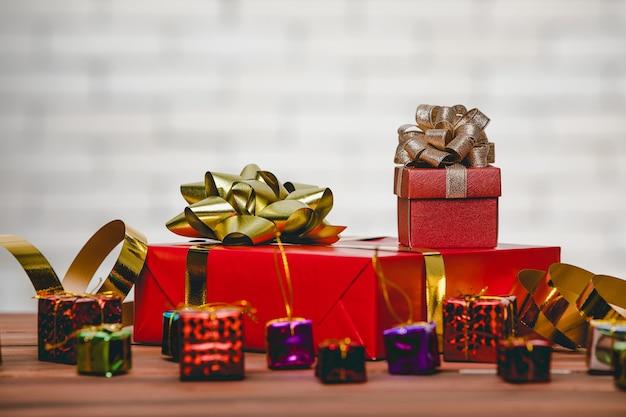Studioaufnahme von großem rotem papier eingewickeltem geschenk mit goldener und silberner schleife und kleinen dekorativen mockup-hängeboxen auf holztisch vor weißer backsteinmauer verschwommener hintergrund.