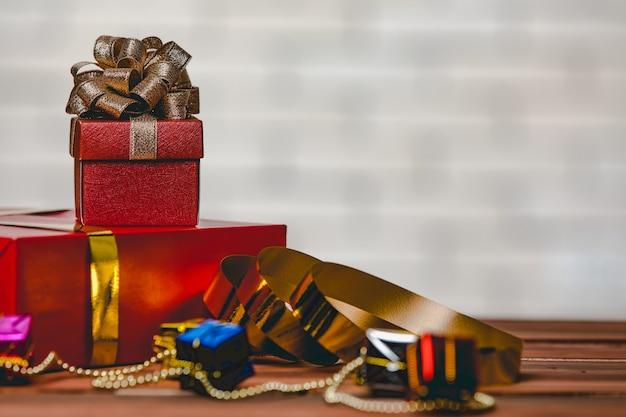 Studioaufnahme von kleinen und großen roten papier eingewickelten geschenkboxen mit gold- und silberbandfliege auf holztisch mit dekorativer hängender kugelkugel vor dem vollen dekor weihnachtskiefer.