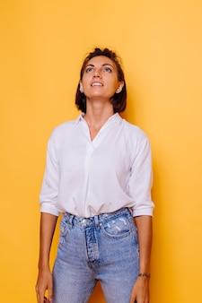 Studioaufnahme von kurzen haaren der glücklichen frau, die weißes hemd und jeanshosen tragen, die auf gelber wand aufwerfen
