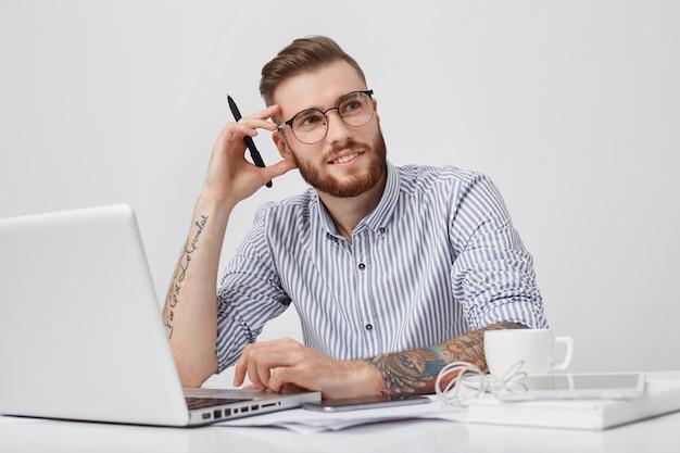 Studioaufnahme von nachdenklichen kreativen männlichen arbeiter- oder journalisten-tastaturen auf laptop-computer,