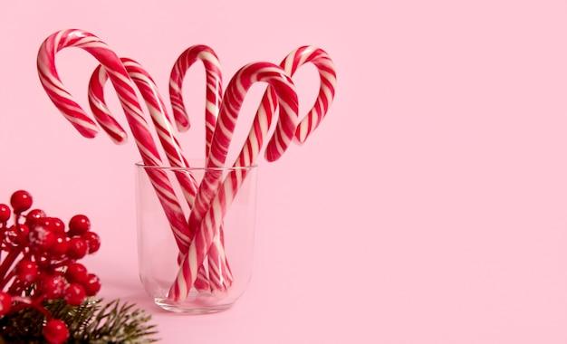 Studioaufnahme von schöner minimalistischer einfacher komposition mit weihnachtslutschern in transparentem glas und schneebedecktem kiefernzweig mit roten beeren, stechpalme, auf rosafarbenem hintergrund mit kopienraum für werbung