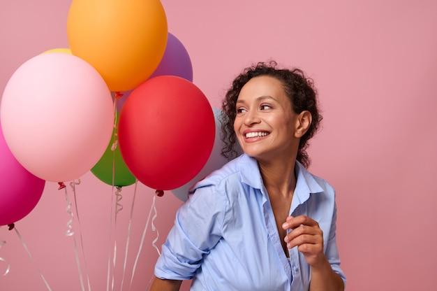 Studioaufnahme von unbeschwerter frau tanzt und hat spaß in blauem hemd und jeansshorts, hat festliche stimmung, posiert vor rosa wandhintergrund mit aufgeblasenen ballons konzept der zeit zum feiern.