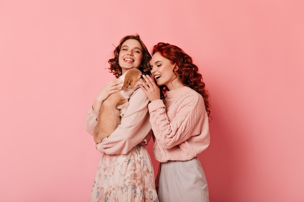 Studioaufnahme von zwei freunden mit hund. lockige mädchen spielen mit welpen auf rosa hintergrund.