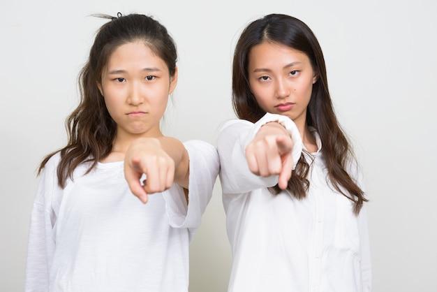 Studioaufnahme von zwei jungen schönen koreanischen frauen als freunde zusammen vor weißem hintergrund
