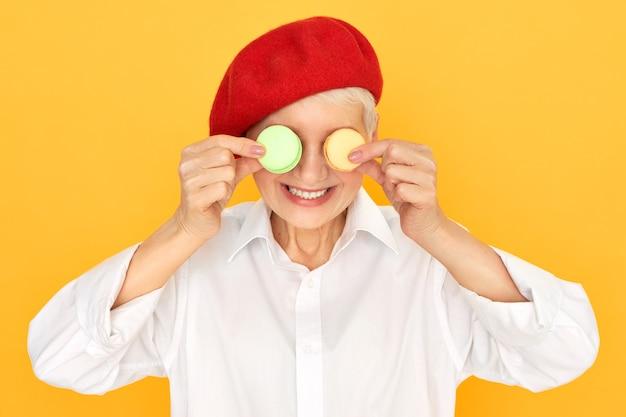 Studiobild der freudigen pensionierten frau im weißen hemd und im roten bonner, die spaß haben, zwei runde französische kekse auf ihren augen zu halten.