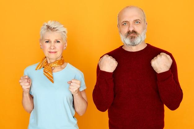 Studiobild des älteren paares, das nebeneinander steht und negative gefühle ausdrückt, wütend auf hohe preise oder niedrige rentenzahlungen ist, geballte fäuste, wütenden wütenden gesichtsausdruck hat