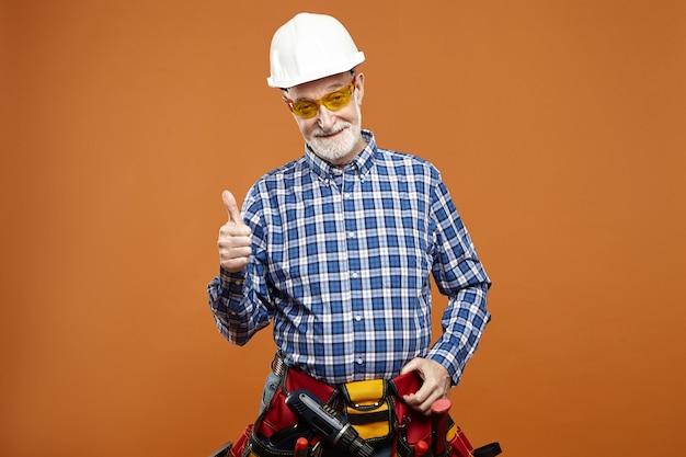 Studiobild des fröhlichen glücklichen älteren älteren bärtigen reparaturmanns, der helm trägt