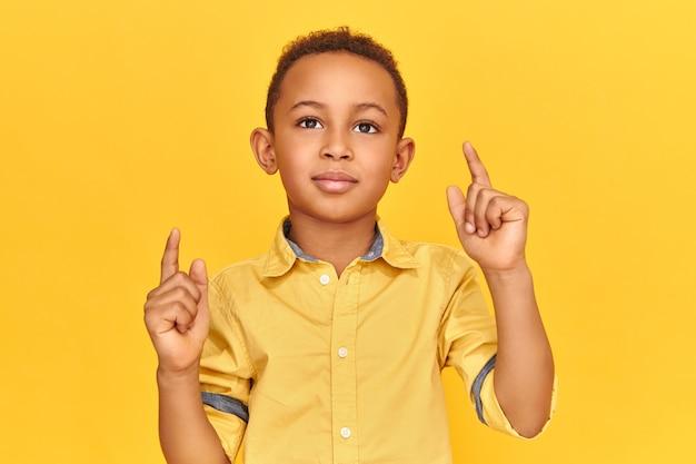 Studiobild des selbstbewussten kühlen dunkelhäutigen kleinen jungen, der lokal gegen gelben wandhintergrund zeigt, der vorderfinger nach oben zeigt und kopienraum f anzeigt