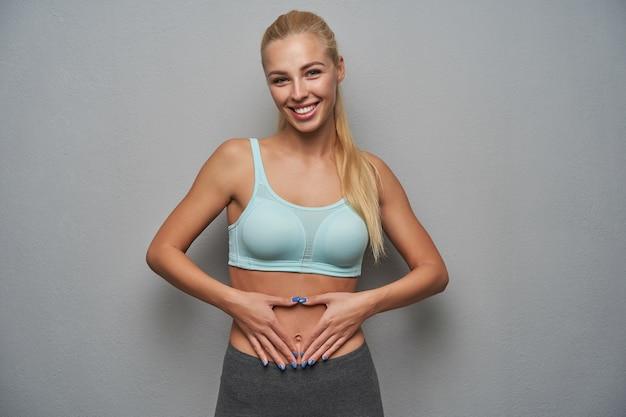 Studiofoto der attraktiven sportlichen jungen dame mit langen blonden haaren, die minzoberteil und graue leggins tragen, während sie gegen hellgrauen hintergrund stehen, glücklich lächeln und handflächen auf ihrem körper halten