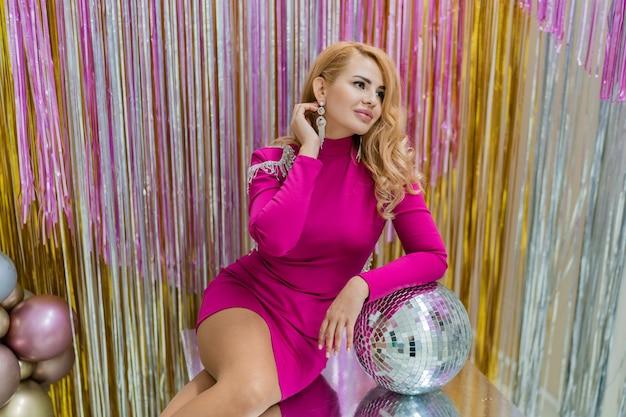 Studiofoto der blonden frau des glamours im rosa luxuskleid, das mit discokugel aufwirft