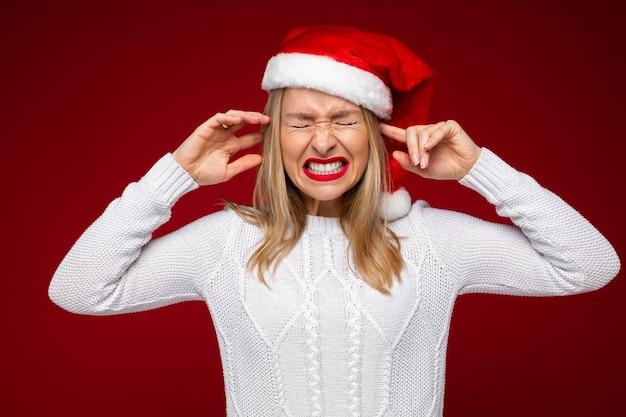 Studiofoto der gestressten jungen dame, die ihre augen und ohren schließt und beim tragen der weihnachtsmütze zusammenzuckt
