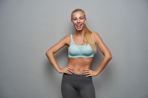 Studiofoto der glücklichen jungen schlanken frau mit den langen blonden haaren, die hände auf ihrer taille halten und freudig in die kamera schauen, minze sportliches oberteil und graue leggins über grauem hintergrund tragend