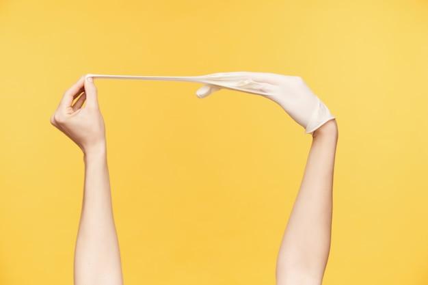 Studiofoto der hände der jungen frau, die über orange hintergrund aufstellen, wobei eine hand mittelfinger zieht, während weißer gummihandschuh herausgenommen wird. konzept der menschlichen hände