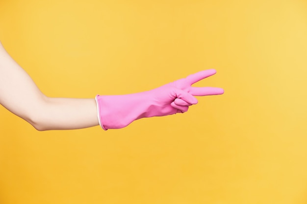 Studiofoto der hand der jungen frau im gummihandschuh, der siegesgeste mit zwei fingern bildet, während über orange hintergrund lokalisiert wird. zeichen und gestik konzept