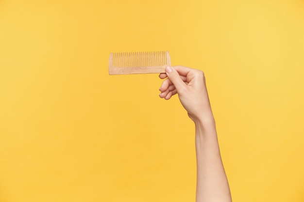 Studiofoto der hand der jungen frau mit der nackten maniküre, die haarbürste horizontal hält, während sie über orange hintergrund aufwirft. haarpflege- und menschenhandkonzept
