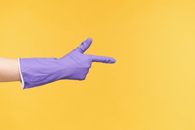 Studiofoto der hellhäutigen hand im gummihandschuh, der angehoben wird, während er mit zeigefinger beiseite zeigt, lokalisiert über gelbem hintergrund während des reinigens des hauses