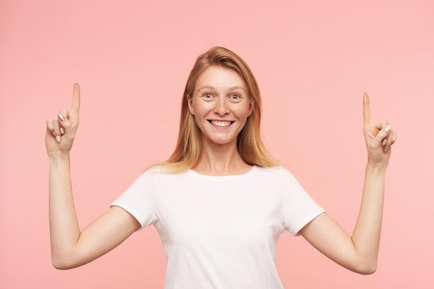 Studiofoto der jungen attraktiven frau mit dem losen foxy haar, das fröhlich in die kamera lächelt und zeigefinger angehoben hält, über rosa hintergrund stehend