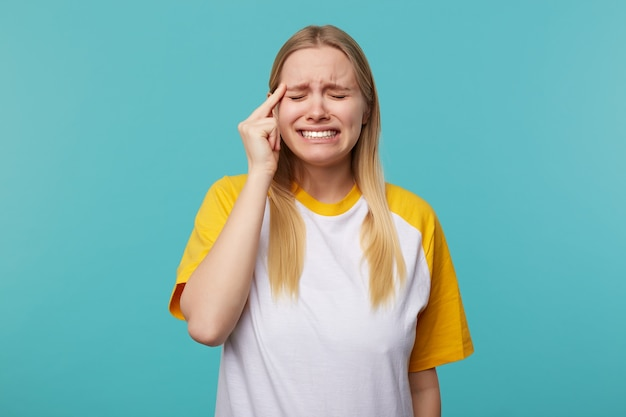 Studiofoto der jungen depressiven langhaarigen blonden frau, die ihre augen geschlossen hält, während sie unglücklich ihr gesicht runzelt, isoliert über blauem hintergrund mit erhabener hand