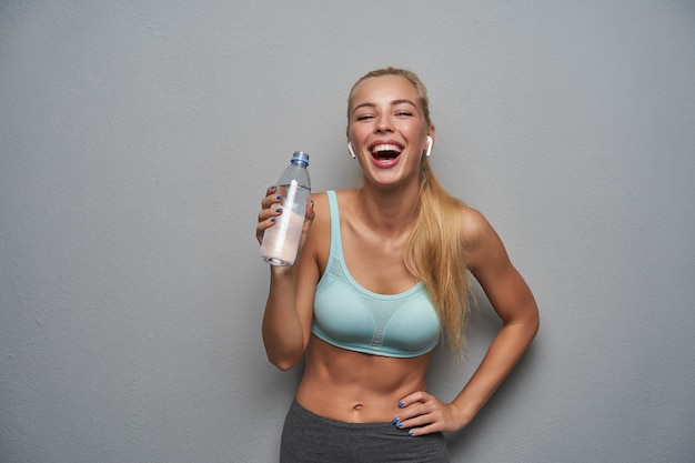 Studiofoto der jungen gesunden blonden frau, die wasser in flaschen hält und hand auf ihrer taille hält, glücklich lachend, während sie über grauem hintergrund steht, gekleidet in sportliche kleidung