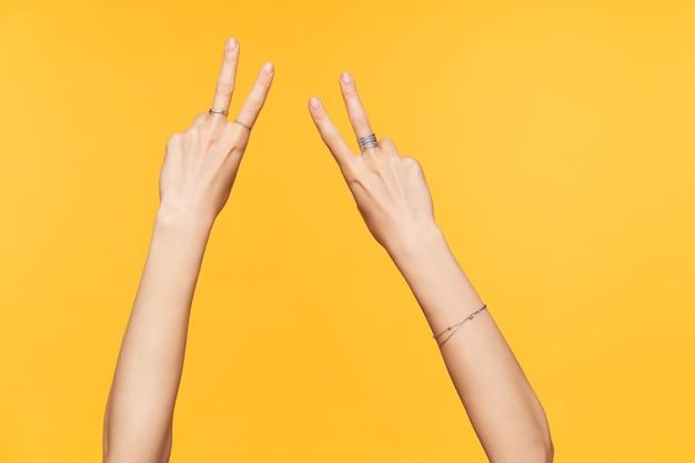 Studiofoto der jungen hellhäutigen weiblichen hände mit der nackten maniküre, die finger erhöht hält, während sie die siegesgeste zeigt, lokalisiert gegen gelben hintergrund