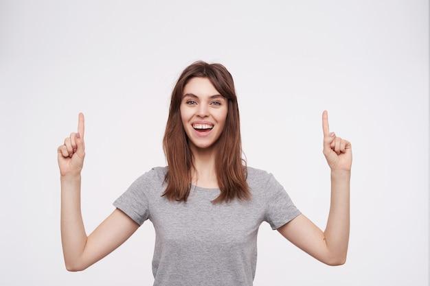 Studiofoto der jungen langhaarigen brünetten frau, die glücklich in die kamera schaut, während sie mit erhabenen zeigefingern nach oben zeigt und über weißem hintergrund steht