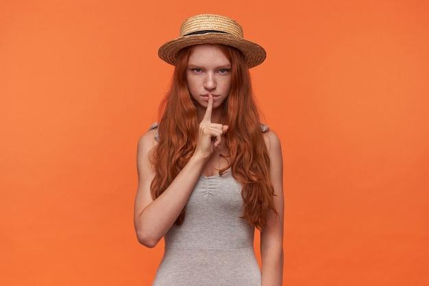 Studiofoto der schönen jungen foxy londhaarigen frau, die zeigefinger in der stillen geste anhebt, zur kamera mit ernstem gesicht schaut und zur stille ruft, lokalisiert über orange hintergrund