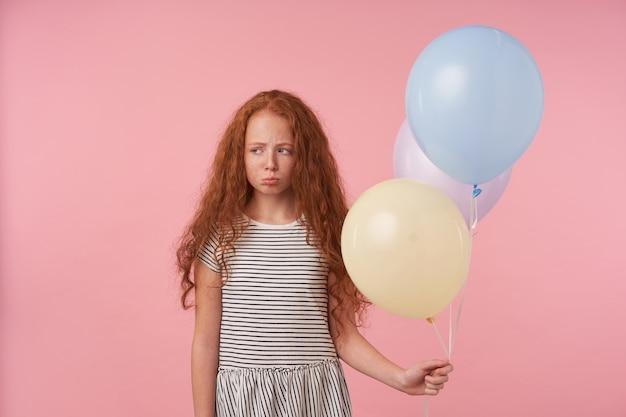 Studiofoto des beleidigten kleinen mädchens mit foxy lockigem haar, das über rosa hintergrund mit farbigen luftballons aufwirft, traurig beiseite schaut und lippen faltet, in böser stimmung ist, gestreiftes kleid trägt