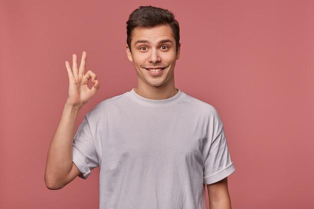 Studiofoto des freudigen jungen braunäugigen mannes mit dunklem haar, das über rosa hintergrund im grauen t-shirt aufwirft, glücklich zur kamera schaut und weit lächelt, hand mit ok geste hebend