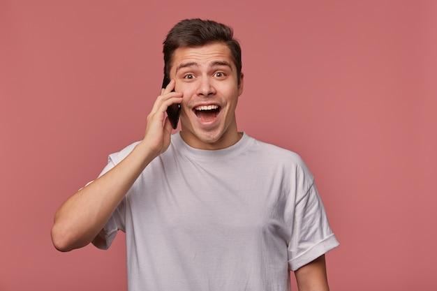 Studiofoto des jungen hübschen dunkelhaarigen mannes mit dem kurzen haarschnitt, der über rosa hintergrund aufwirft, zur kamera glücklich mit geöffnetem weitem mund schauend, handy in der hand haltend