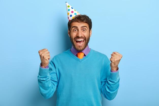 Studiofoto des überglücklichen kerls mit geburtstagshut, der im blauen pullover aufwirft