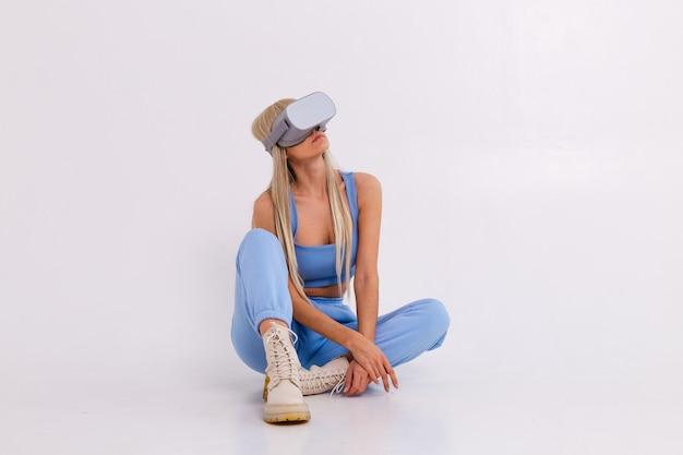 Studiofoto einer jungen attraktiven frau in einem warmen blauen modischen anzug, der eine brille der virtuellen realität trägt