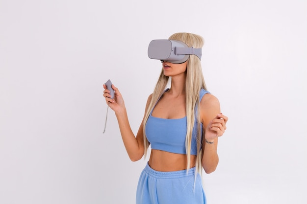 Studiofoto einer jungen attraktiven frau in einem warmen blauen modischen anzug, der eine virtual-reality-brille auf einem weiß trägt