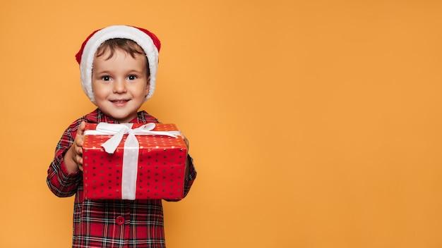 Studiofoto eines babys im weihnachtspyjama und eines hutes auf gelbem hintergrund mit einer leuchtend roten geschenkbox in seinen händen. ein platz für ihren text, ihre werbung.