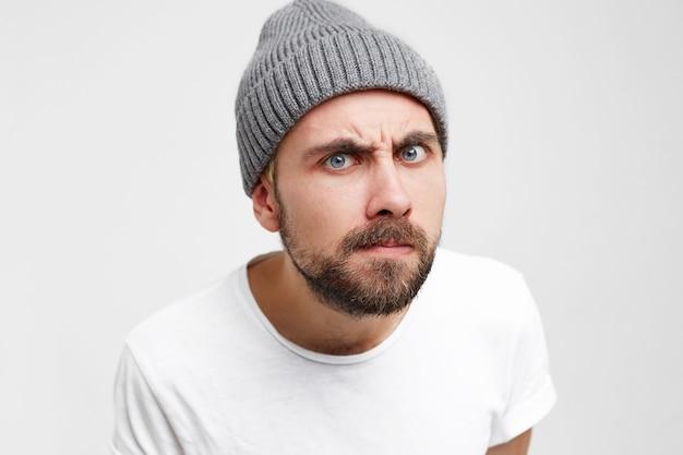 Studiofoto eines jungen mannes, als würde er interessiert in das guckloch schauen, schrill, akribisch