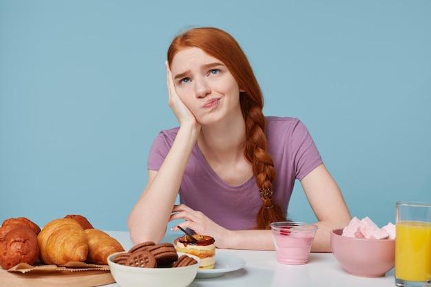 Studiofoto eines traurigen rothaarigen mädchens, zweifel, die über lebensmittel, gesundheit, ernährung, zusätzliche kalorien, backwaren und frisches obst nachdenken