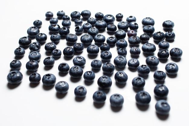 Studiofoto von blaubeeren verbreitete sich auf dem weißen tisch.
