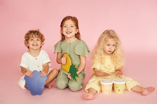 Studiofoto von fröhlichen kindern auf rosa hintergrund. dekorative früchte in händen
