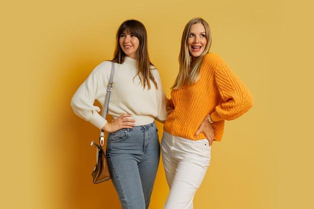 Studiofoto von zwei hübschen frauen in gemütlichen pullovern, die auf gelb posieren. modetrends im herbst und winter.