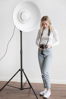 Studiolampe und frau, die ein kamerafoto halten