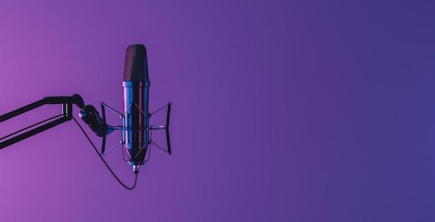 Studiomikrofon auf dunklem hintergrund mit neonbeleuchtung und platz für text isoliert. 3d-rendering
