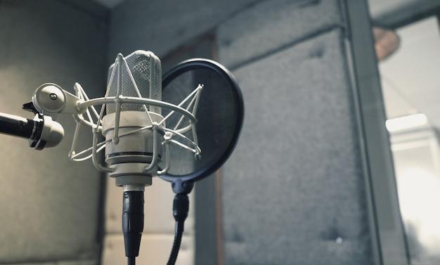 Studiomikrofon mit shock mount und poppfilter auf professionellem stativ im akustikschaumraum
