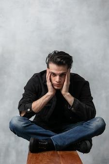 Studiomodeporträt des attraktiven jungen mannes in der schwarzen jacke und in blue jeans, die auf holzbank gegen graue strukturierte wand sitzen.