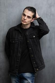 Studiomodeporträt des attraktiven jungen mannes in der schwarzen jacke und in den blauen jeans, die über graue strukturierte wand stehen.