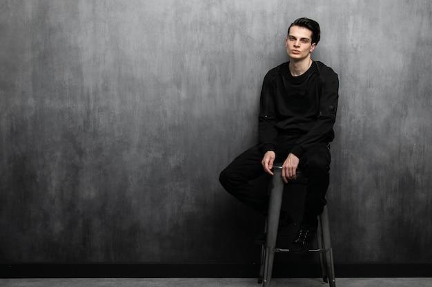 Studiomodeporträt des jungen sexy mannes im schwarzen hoodie und in den jeans.
