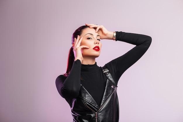 Studiomodeporträt schicke schöne junge frau mit sexy roten lippen mit braunem haar in schwarzer modischer lederkleidung auf hellem hintergrund im raum. stilvolles modell des modernen mädchens, das zuhause aufwirft.
